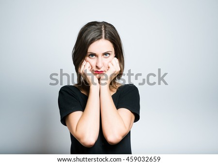 Young business woman props chin, studio photo isolated on a gray background