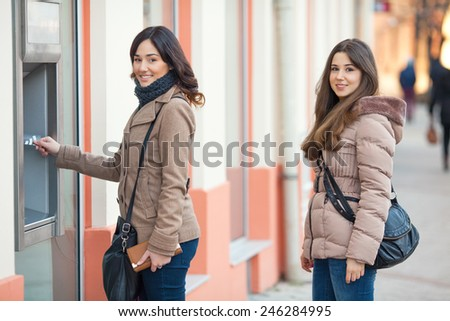 Young business woman putting her credit card at the ATM and looking at camera. - stock photo