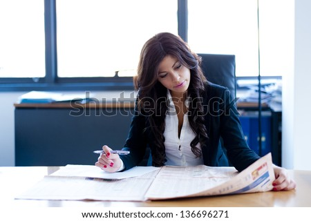 young business woman reading sitting at the desk on office background - stock photo