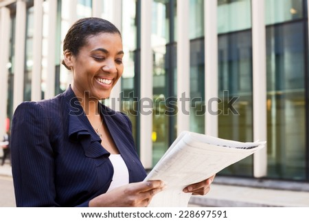 young business woman reading the newspaper - stock photo