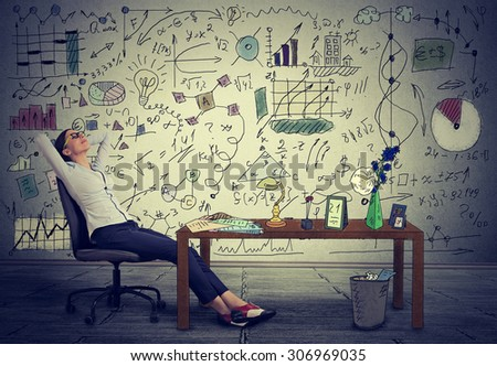 Young business woman relaxing at her desk in her office  - stock photo