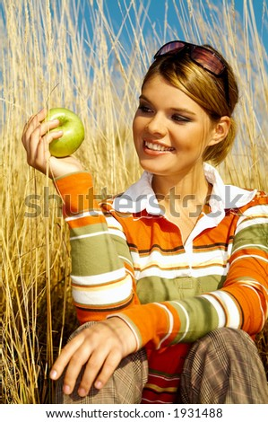 Young business woman relaxing on meadow, holding green fresh apple