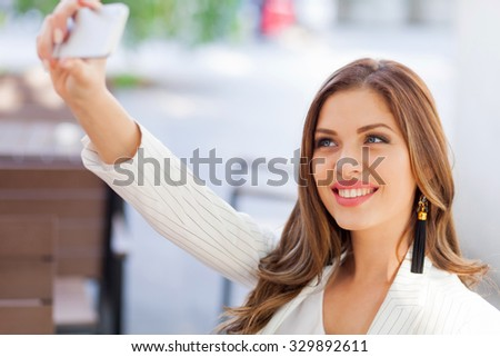Young business woman self photgraphing - stock photo