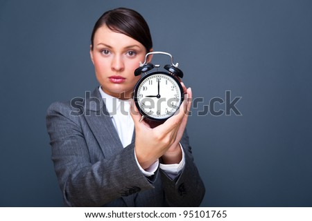 Young business woman showing alarm clock against grey background with copyspace