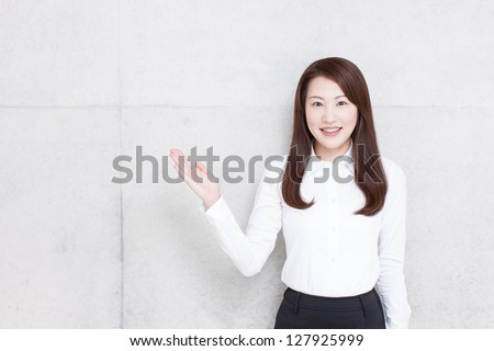 young business woman showing copy space against concrete wall - stock photo