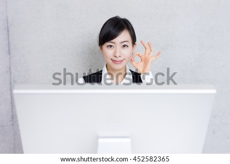 young business woman showing OK gesture with computer at office - stock photo