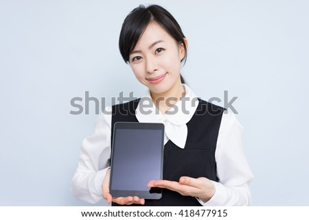Young business woman showing tablet computer against blue background - stock photo