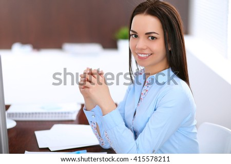 Young business woman sitting and writing at the table  in office