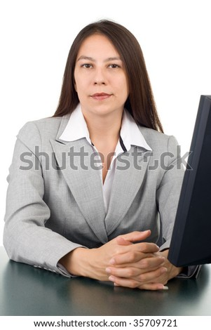 Young business woman sitting at the desk with computer monitor - stock photo