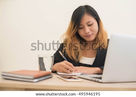 young business woman sitting at workplace and Writing notes in a notebook in office