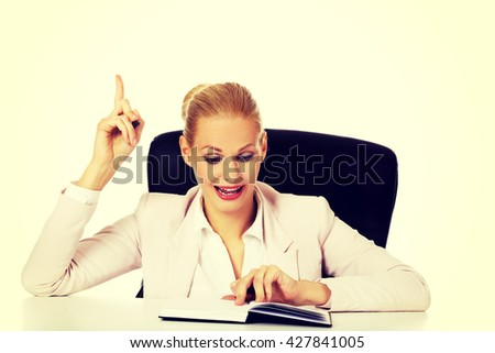 Young business woman sitting behind the desk and having idea  - stock photo