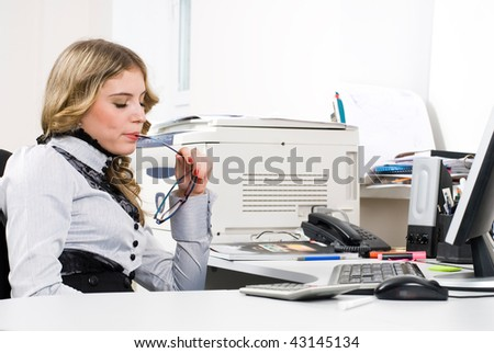 Young business woman sitting in front of computer monitor in office