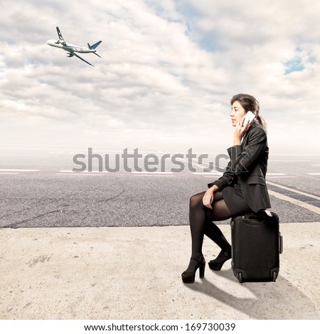 young business woman sitting on a suitcase at the airport - stock photo
