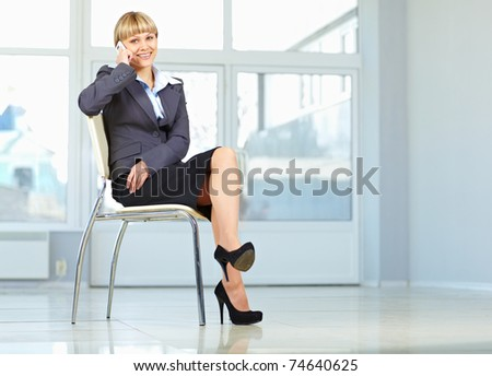 Young business woman sitting on chair and using mobile phone - stock photo