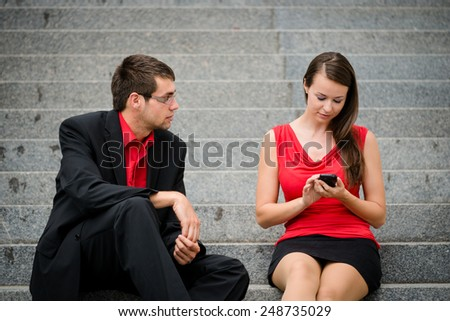 Young business woman sitting on stairs and working with smartphone while man is bored and angry - stock photo