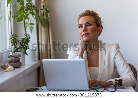 Young business woman sitting with laptop thoughtfully dreamy looks in the space. - stock photo
