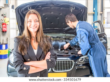 Young business woman, smiling and looking into the camera, whilst a mechanic tends to the maintenance of her car in the background at a dedicated professional garage - stock photo