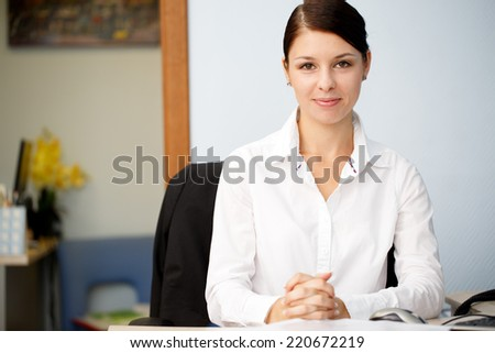 Young business woman smiling at office - stock photo