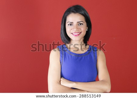 Young business woman smiling with her arms crossed and looking confident - stock photo
