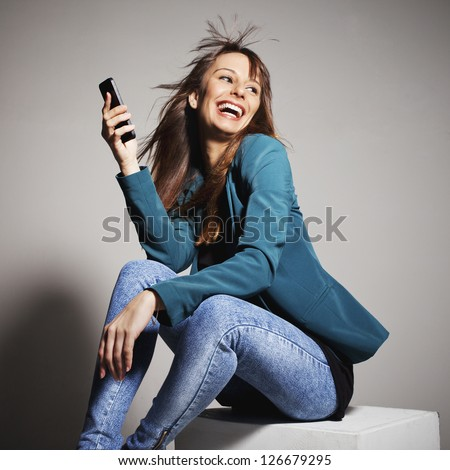 Young business woman smiling with smart phone. Beautiful business woman with mobile phone. On a grey background - stock photo