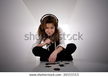 Young business woman solving a puzzle problem in white cube space - stock photo