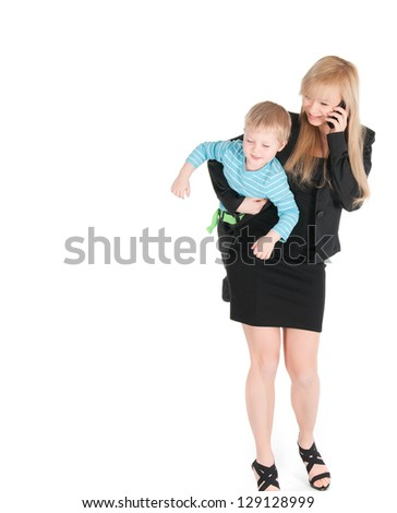 Young business woman speaking by phone and carrying her son under arm over white background.