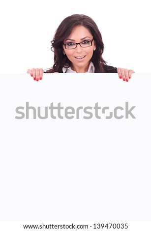 young business woman standing behind an empty board and smiling to the camera. on white background - stock photo