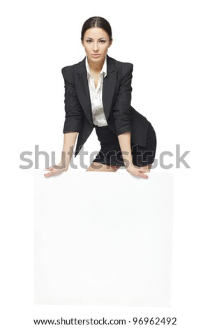 Young business woman standing behind and leaning on a white blank billboard / placard, isolated on white background - stock photo