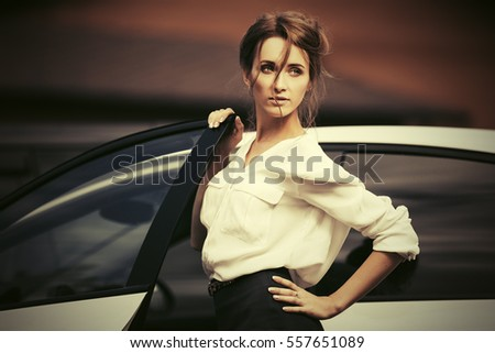 Young business woman standing beside her car  Stylish fashion model outdoor