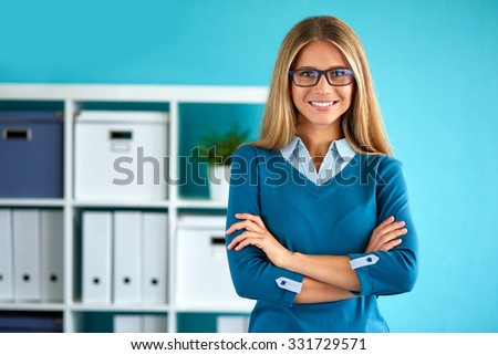 Young business woman standing in office with crossed arms - stock photo