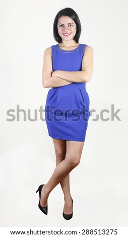 Young business woman standing wearing a blue dress with her arms crossed - stock photo