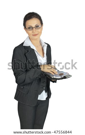 Young business woman stands, holding a business organizer and smiles, looking to the left. On a white background - stock photo