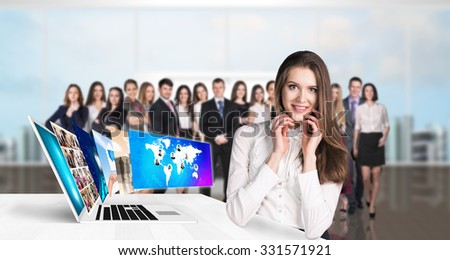 Young business woman stands near table with laptop. Elements of this image furnished by NASA. - stock photo