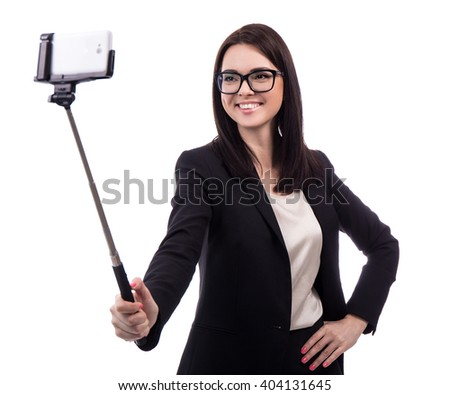 young business woman taking photo with smart phone on selfie stick isolated on white background - stock photo