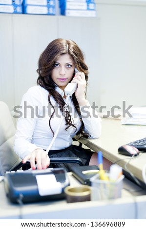 young business woman talking at the phone sitting at the desk on office background