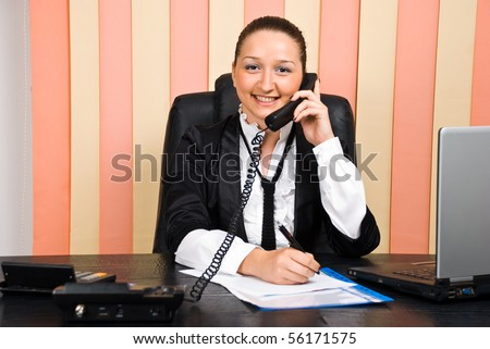 Young business woman talking by telephone and taking notes