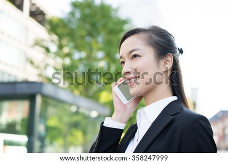 Young business woman talking on a smart phone. - stock photo