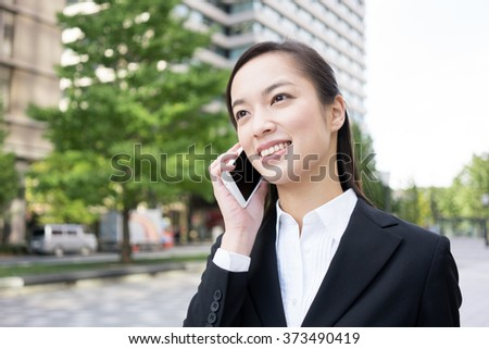 Young business woman talking on a smart phone - stock photo