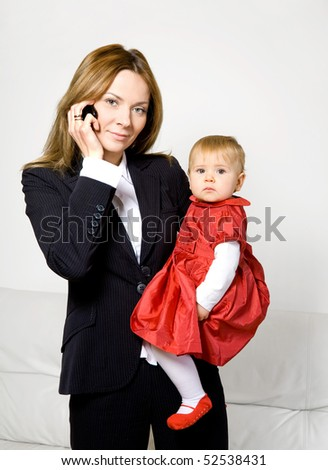 young business woman  talking on cell phone with her baby girl - stock photo