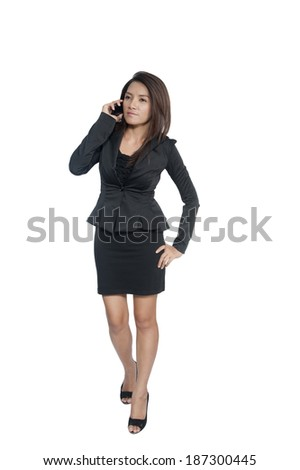 Young business woman talking on cellphone, full length portrait on white background - stock photo