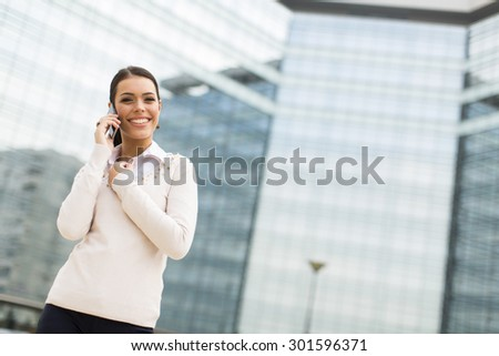 Young business woman talking on mobile phone in front of office building - stock photo
