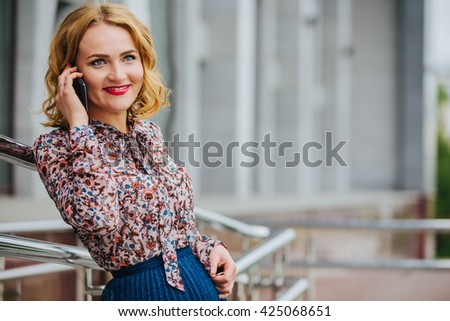 young business woman talking on phone in the city