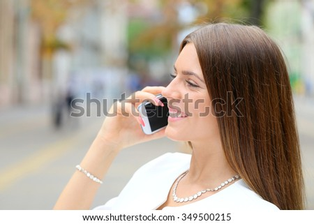 young business woman talking on phone on city walking street - stock photo