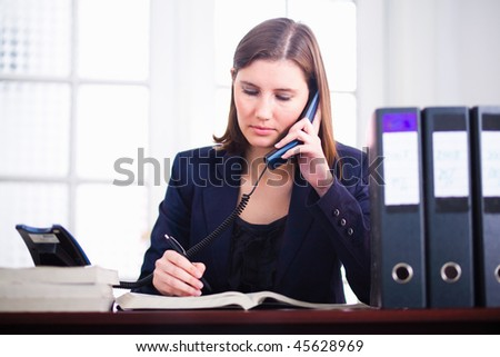Young business woman talking on the phone and writing in book. - stock photo