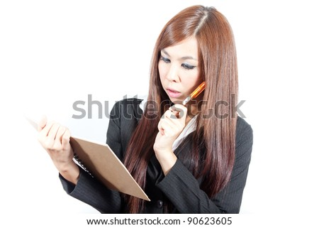 Young business woman thinking with her note and pen - stock photo