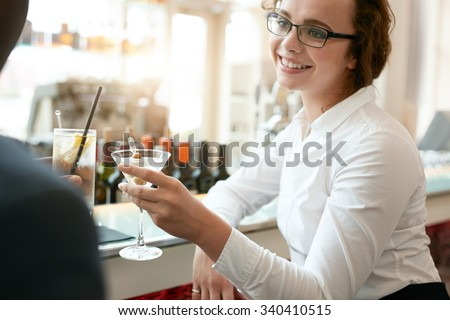 Young business woman toasting drinks with colleague at cafe. Caucasian businesswoman with partner having a glass of drink at bar after work. - stock photo