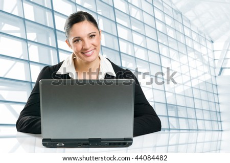 Young business woman typing on her laptop in a modern office