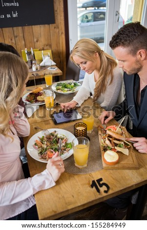 Young business woman using digital tablet while sitting with colleagues at cafe - stock photo