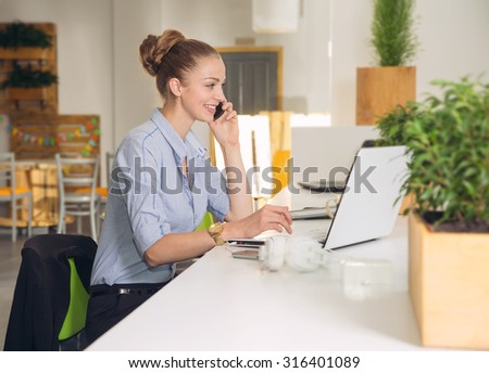Young business woman using laptop at office. Beautiful business woman working on computer at her office. She is a sales manager or an insurance agent. Young business woman with notebook in the office - stock photo