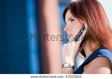 Young business woman using mobile cell phone over city background. Student - stock photo